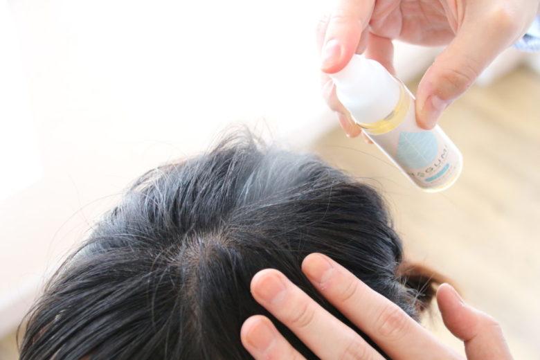 「フケ」「かゆみ」頭皮のトラブルのための頭皮の美容液〔はぐみヘアトニック〕を頭皮にスプレーしている画像